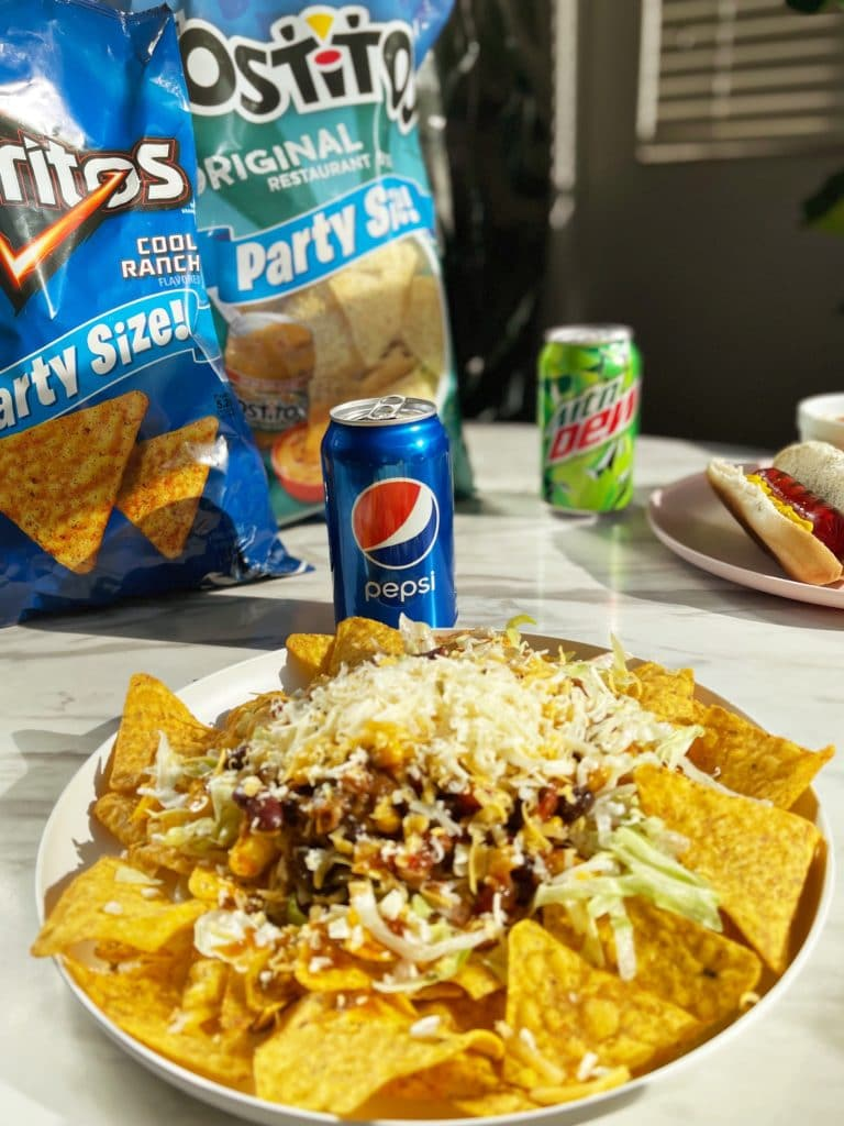A haystack in front of an open can of pepsi and a bag of Cool Ranch Doritos and a bag of Tostitos.